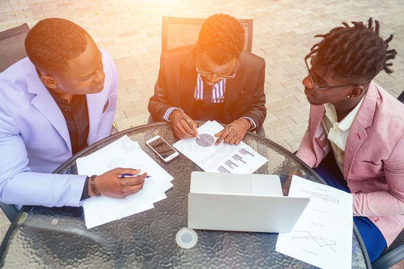 Group of three black afro american men in stylish business suit, expensive wristwatch and tie sit at the round table. With laptop, securities and contracts stock image
