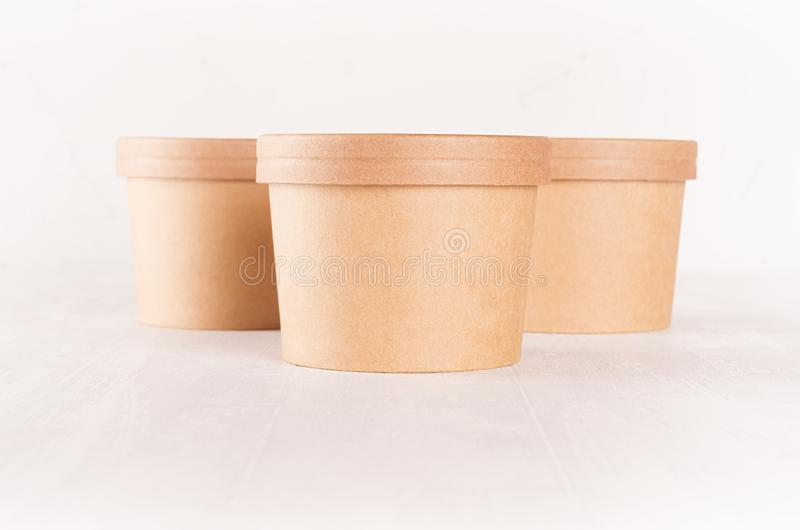 Group of three blank disposable brown paper boxs for takeaway food with caps - soup, salad, ice cream on white wood shelf closeup. royalty free stock photography