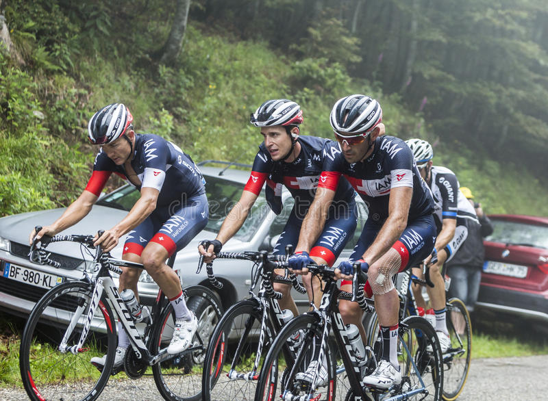 Group of Three Cyclists - Tour de France 2014. Col de Platzerwasel,France - July 14, 2014: Group of three cylists of IAM Cycling Team riding on the climbing road royalty free stock photo
