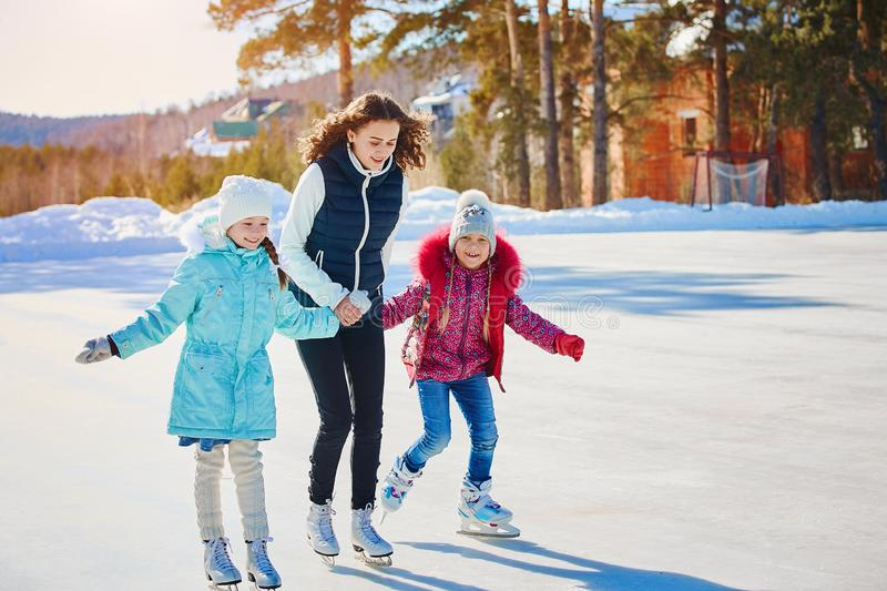 A group of three girls on a winter skating rink. Roll and laugh. Skating rink in nature. A group of three girls on a winter skating rink. Roll and laugh stock images