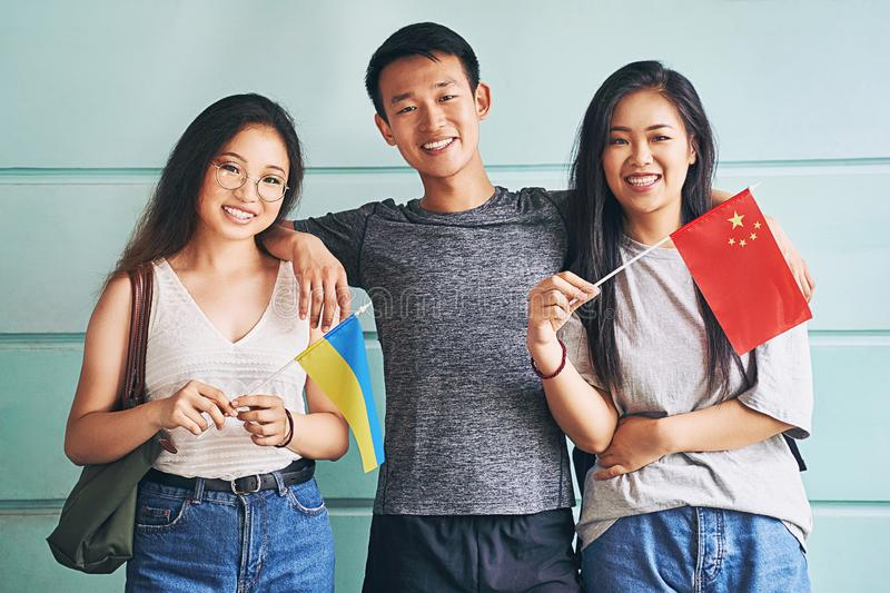 Group of three happy international chinese asian students smiling and holding flags of China and Ukraine in university. Group of three international chinese stock photos