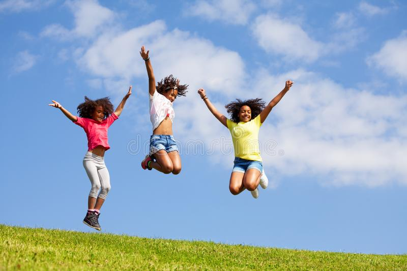 Group three jumping girls over clean blue sky stock photos