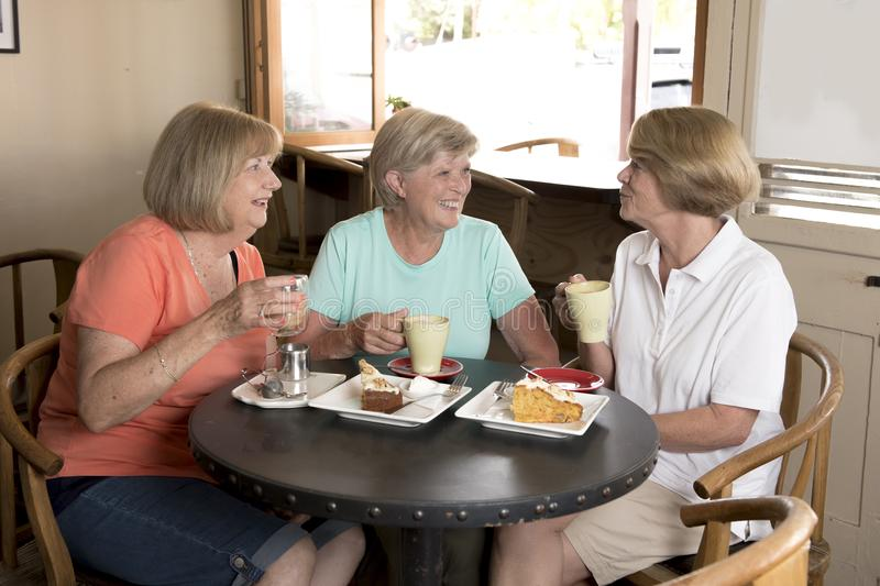 Group of three lovely middle age senior mature women girlfriends meeting for coffee and tea with cakes at coffee shop sharing time. Together enjoying stock photography