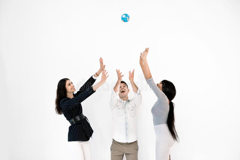 Group of three multiethnical international happy people throwing up little globe earth and looking up while it is royalty free stock image