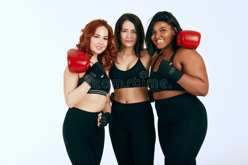 Three multiracial diverse woman in black sportswear posing in boxing gloves stock photos
