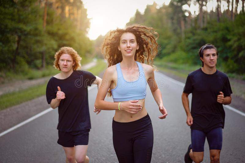 A group of three people athletes one girl and two men run on an asphalt road in a pine forest. A group of three people athletes one girl and two men run on royalty free stock photos