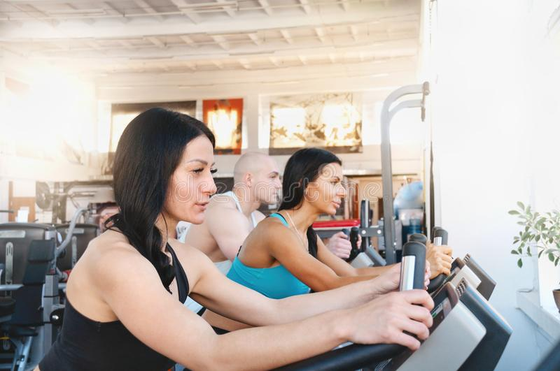 Group of three people in the gym, exercising their legs doing cardio training royalty free stock photo