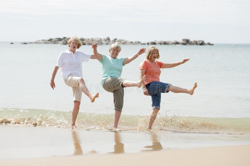 Group of three senior mature retired women on their 60s having fun enjoying together happy walking on the beach smiling playful stock image