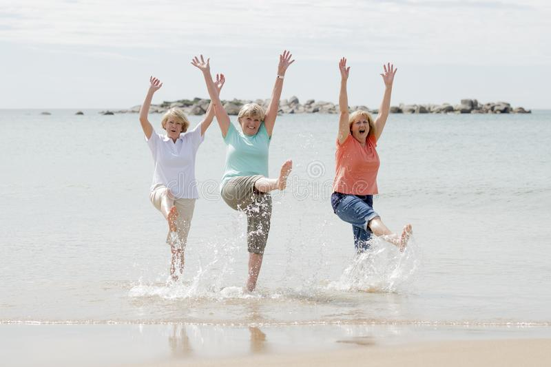 Group of three senior mature retired women on their 60s having fun enjoying together happy walking on the beach smiling playful. Lovely group of three senior stock photos