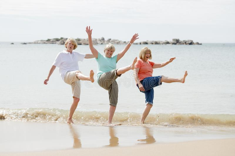 Group of three senior mature retired women on their 60s having fun enjoying together happy walking on the beach smiling playful. Lovely group of three senior royalty free stock images