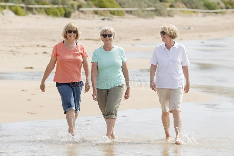 Group of three senior mature retired women on their 60s having fun enjoying together happy walking on the beach smiling playful. Lovely group of three senior stock photo