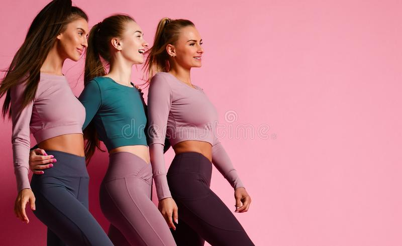 Group of three sport girls international friends posing on pink background. Sporty young women in green and purple royalty free stock photos