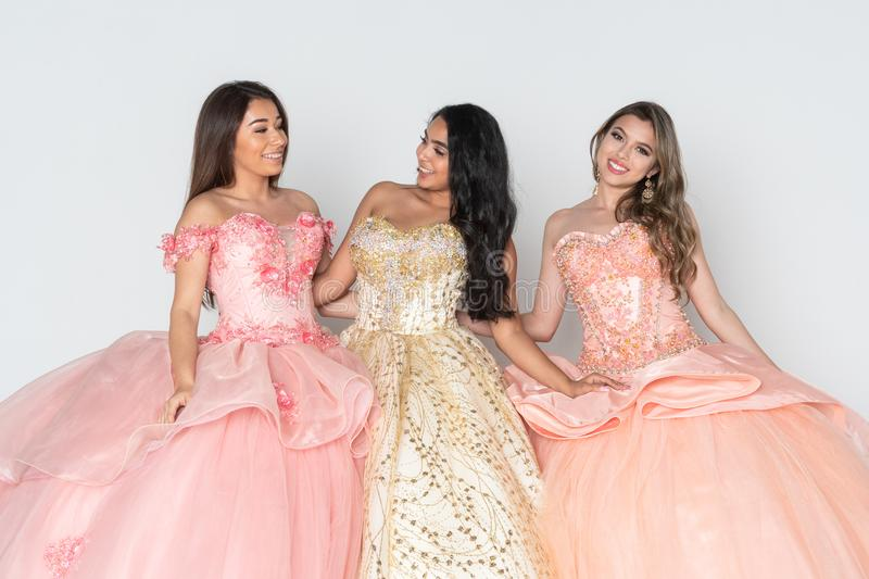 Teen Girls In Quinceanera Dresses. Group of three teenage hispanic girls wearing quinceanera dresses royalty free stock image