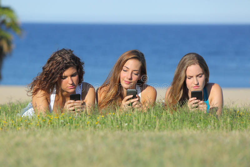 Group of three teenager girls typing on the mobile phone lying on the grass. With the sea in the background royalty free stock images