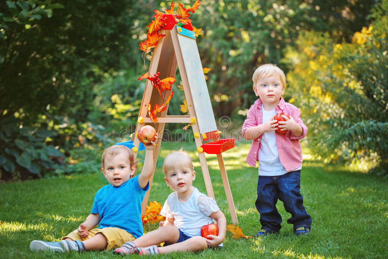 Group of three white Caucasian toddler children kids boys and girl outside in summer autumn park by drawing easel holding apples stock image