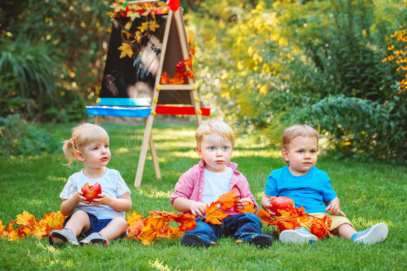 Group of three white Caucasian toddler children kids boys and girl sitting outside in summer autumn park by drawing easel. With fall leaves and apple, back to stock images