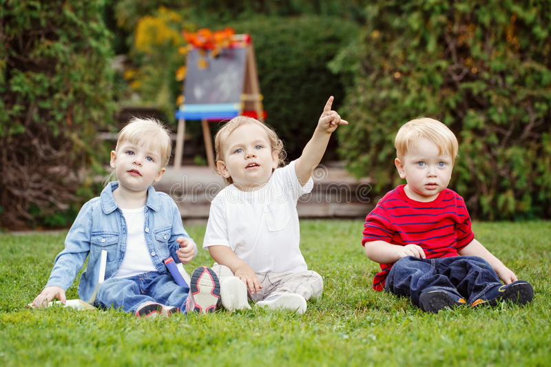 Group of three white Caucasian toddler children kids boys and girl sitting outside in summer autumn park by drawing easel. With fall leaves looking in camera stock photography