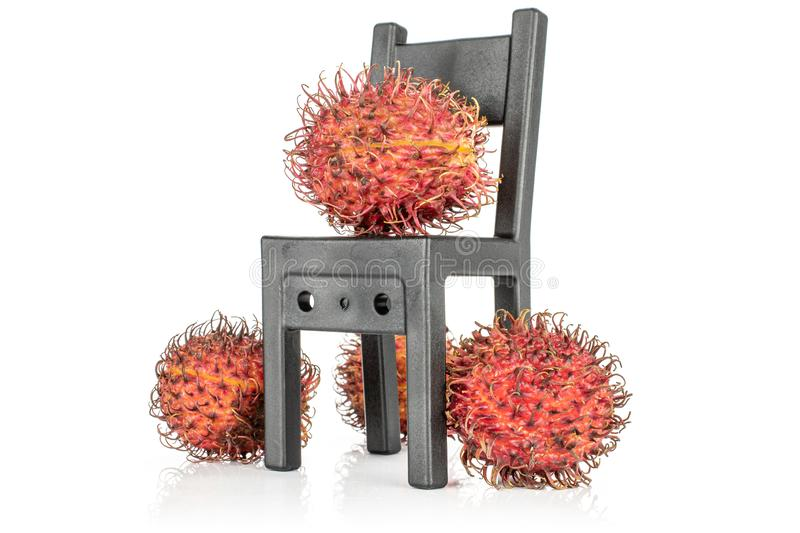 Fresh red rambutan isolated on white. Group of three whole fresh red rambutan with black chair isolated on white background royalty free stock photos