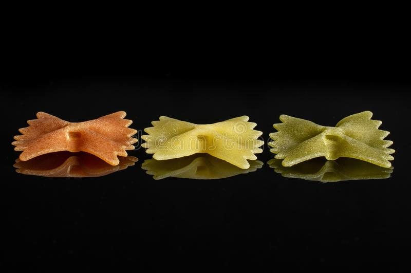 Raw farfalle tricolore isolated on black glass stock images