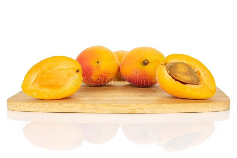 Fresh orange apricot isolated on white. Group of three whole two halves of fresh orange apricot with an apricot stone on a bamboo cutting board isolated on white stock image