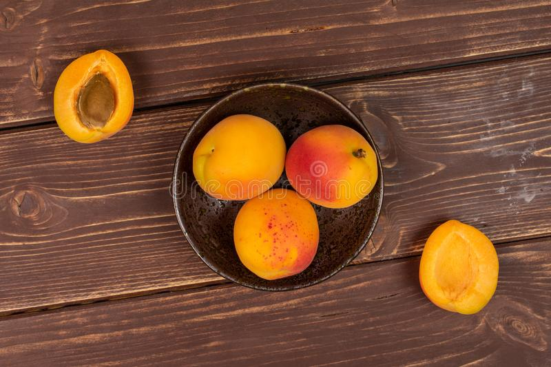 Fresh orange apricot on brown wood. Group of three whole two halves of fresh orange apricot with an apricot stone in a dark ceramic bowl flatlay on brown wood royalty free stock image