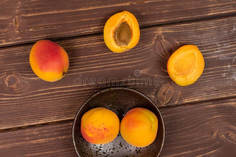 Fresh orange apricot on brown wood. Group of three whole two halves of fresh orange apricot with an apricot stone in a dark ceramic bowl flatlay on brown wood royalty free stock photo