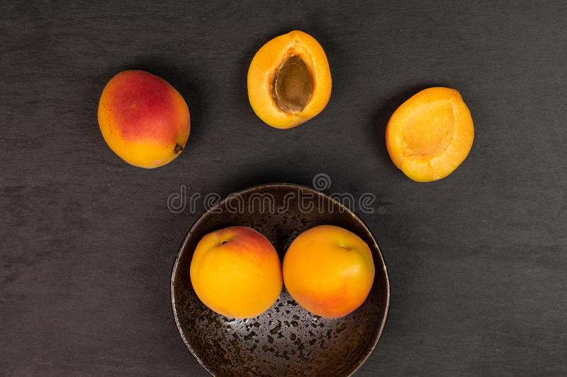 Fresh orange apricot on grey stone. Group of three whole two halves of fresh orange apricot with an apricot stone in a dark ceramic bowl flatlay on grey stone royalty free stock photography