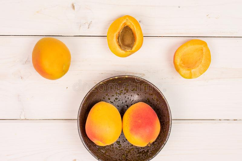 Fresh orange apricot on grey wood. Group of three whole two halves of fresh orange apricot with an apricot stone in a dark ceramic bowl flatlay on white wood stock photography