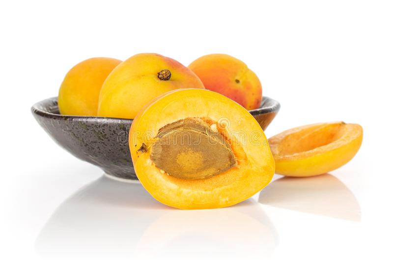 Fresh orange apricot isolated on white. Group of three whole two halves of fresh orange apricot with an apricot stone in a dark ceramic bowl isolated on white royalty free stock image