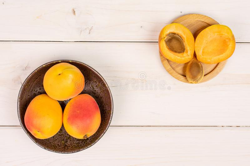 Fresh orange apricot on grey wood. Group of three whole two halves one piece of fresh orange apricot with an apricot stone in a dark ceramic bowl flatlay on royalty free stock images