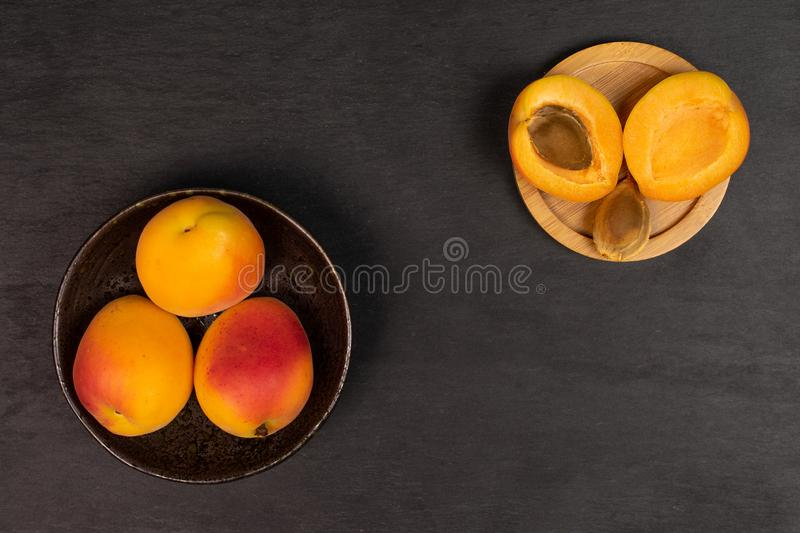 Fresh orange apricot on grey stone. Group of three whole two halves one piece of fresh orange apricot with an apricot stone in a dark ceramic bowl flatlay on stock images