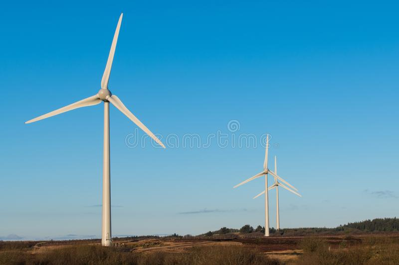 A group of three wind turbines in a wind farm stock image