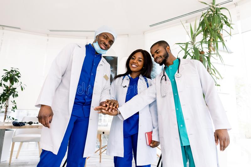 Group of three young African doctors, two men and woman, putting their hands together, standing in modern clinic stock photos