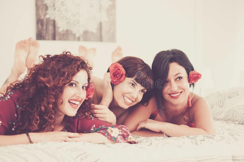 Group of three young cheerful women have fun together laying on the bed ready to go out for the night life - beauty and make up stock image