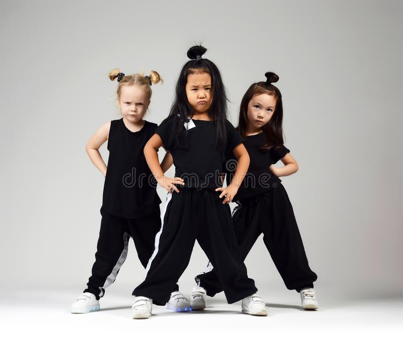 Group of three young girl kids hip hop dancers on gray. Background stock photos