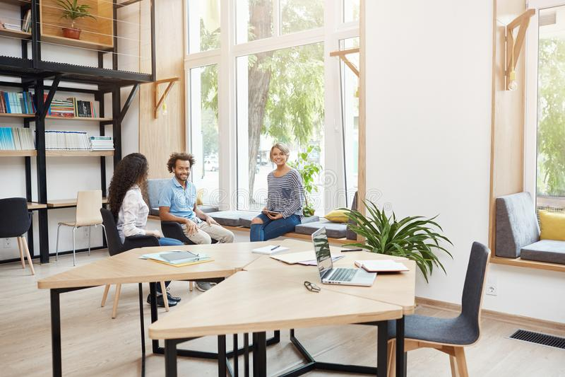 Group of three young multi ethnic startups working together in coworking space, having break from brainstorming. Young royalty free stock images