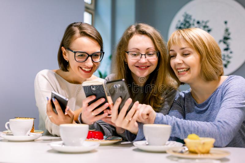 Group of three young women smiling and showing the pictures on the smartphones each other, sitting in restaurant stock photo