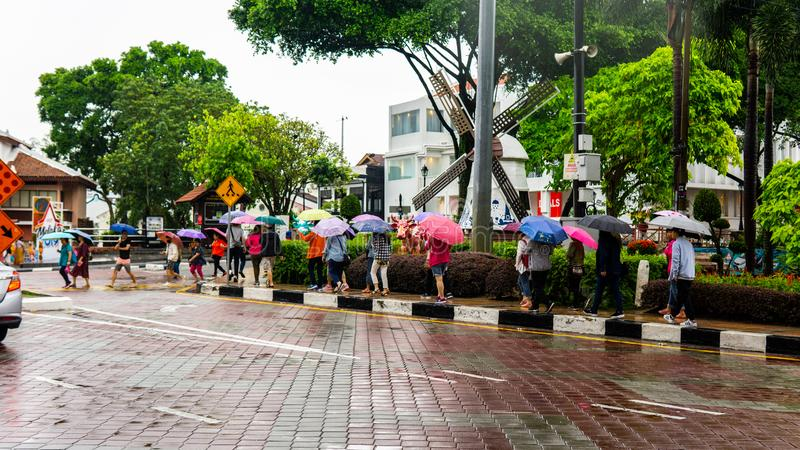Group of tourist walking at the side of the main road with their colorful umbrella during the rainy days in Melaka. Bandar Hilir, Melaka - June 28 stock images