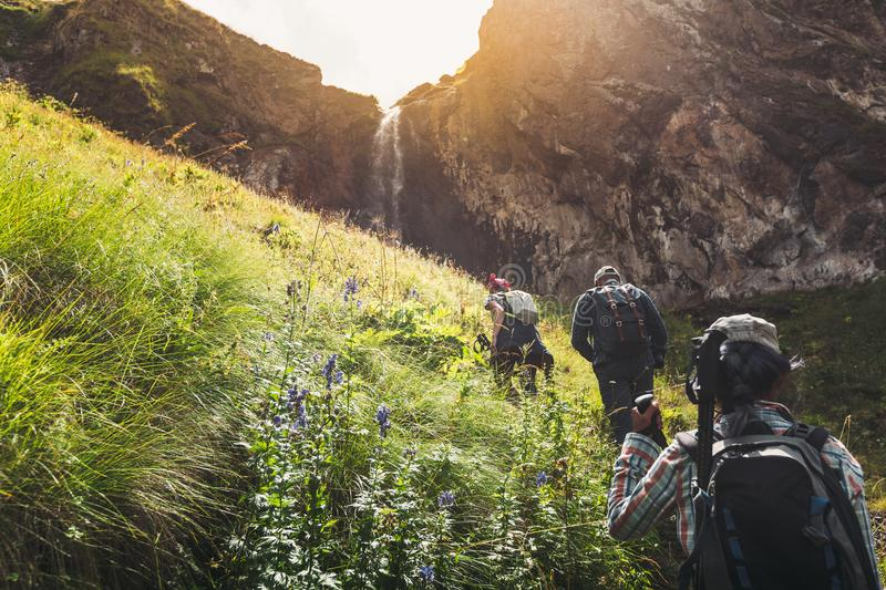 Group Of Tourists Walking Uphill To Waterfall. Travel Adventure Outdoor Concept. A group of tourists with backpacks rises uphill to a picturesque waterfall stock photos