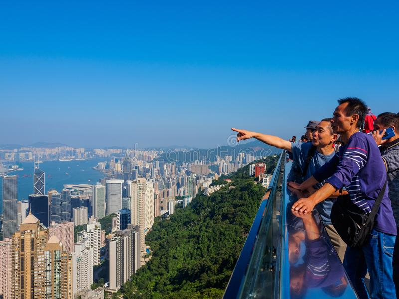 A group of tourists from the Chinese mainland, enjoying the view over Hong Kong from the royalty free stock images