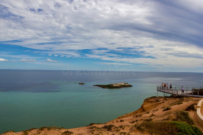 A Group of tourists at a Lookout platform in Monkey Mia, Western Australia. Caucasian girl enjoying cliffs of Indian stock photo
