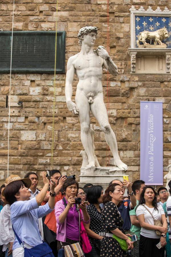 Group of tourists making photos on Palazzo Vecchio, Florence, Italy stock photography