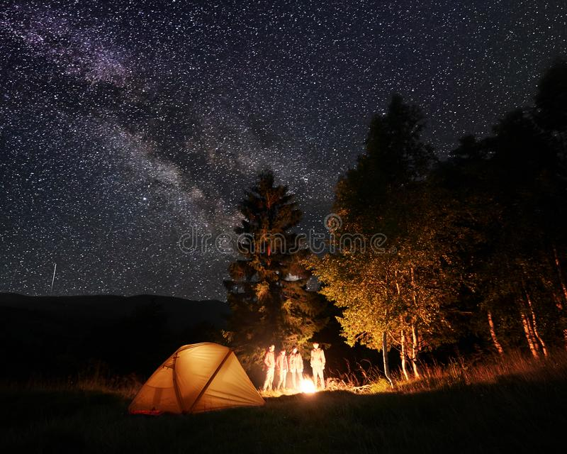 Group of tourists in night forest at tent camp look on burning fire under the starry sky stock photography