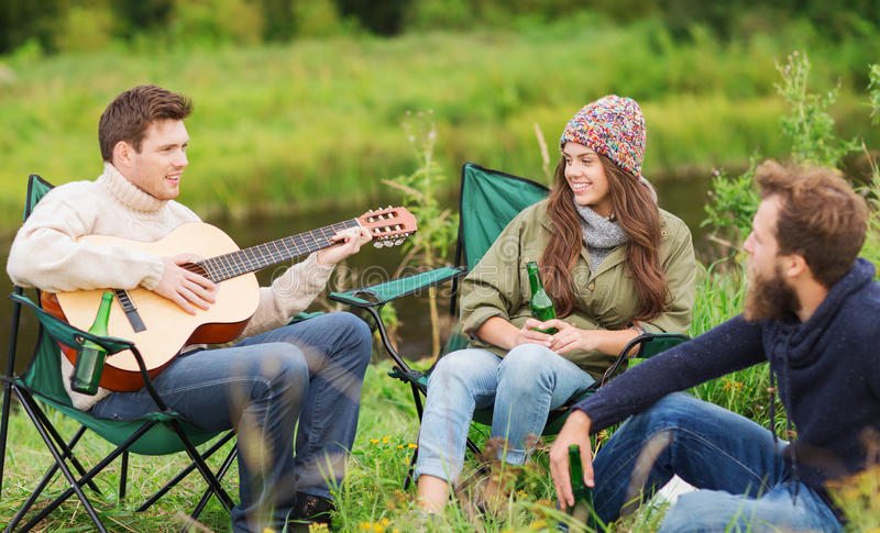 Group of tourists playing guitar in camping. Adventure, travel, tourism and people concept - group of smiling tourists playing guitar and drinking beer in royalty free stock image