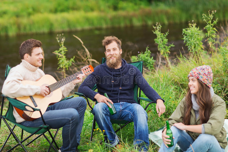 Group of tourists playing guitar in camping. Adventure, travel, tourism and people concept - group of smiling tourists playing guitar and drinking beer in stock photo