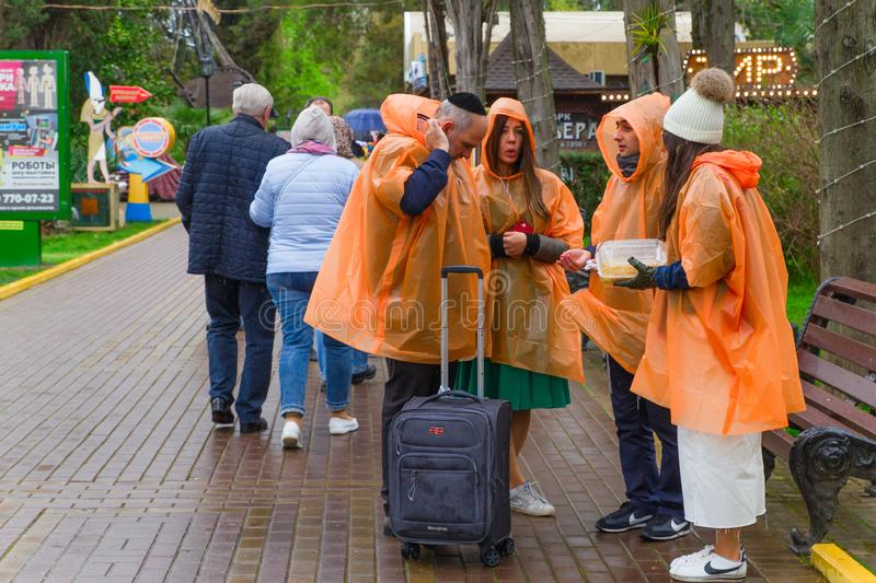 SOCHI,RUSSIA,  21 APRIL 2019 - a group of tourists in the Riviera park dressed in orange raincoats in cloudy weather stock images
