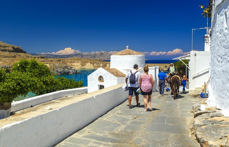 a group of tourists strolling through the streets. Sea skyview landscape photo bay and orthodox church in Lindos on Rhodes island royalty free stock photos