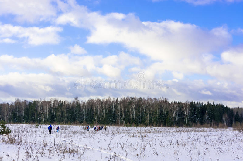 A group of tourists walking through the snowy field. A group of tourists walking through the snowy field on a Sunny winter`s day stock photo