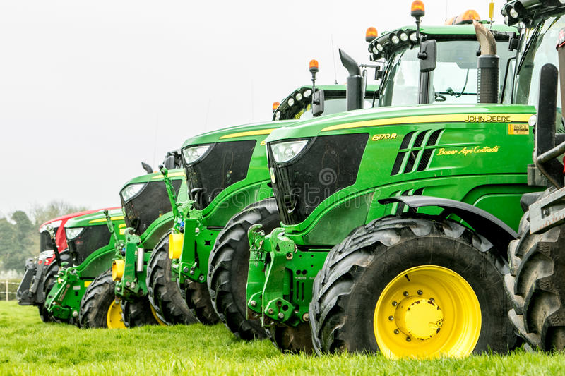 A group of tractors parked up. A group of john deere tractors parked up in a line row all different makes and colours in show royalty free stock image