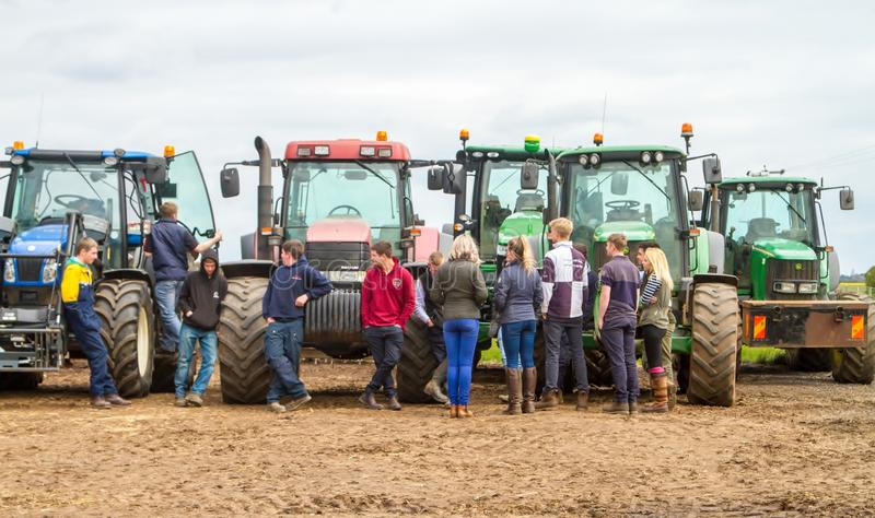 A group of tractors parked up with young farmers royalty free stock image